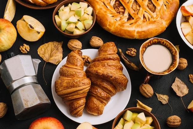 Feuilles et noix au milieu de la pâtisserie et des boissons