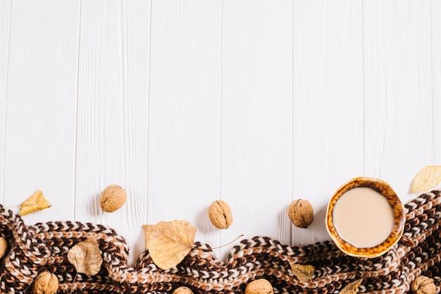 Feuilles et noix près de boisson et écharpe