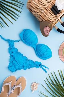 Feuilles de palmier, chapeau de mode, bikini, tongs, sac de plage de paille sur une surface bleu pastel clair, concept de voyage et vacances, vue de dessus