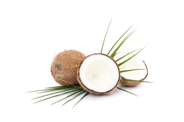Feuilles de palmier, noix de coco et deux moitiés isolés sur fond blanc. fruits exotiques