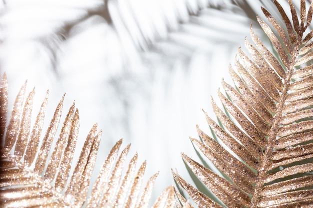 Les feuilles de palmier d'or et les ombres sur un fond de mur bleu.