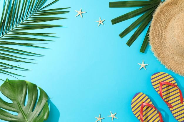 Feuilles de palmier, tongs, chapeau et étoiles de mer sur table bleue