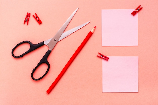 Feuilles de papeterie pour les notes coupées, crayon et ciseaux sur la vue de dessus rouge