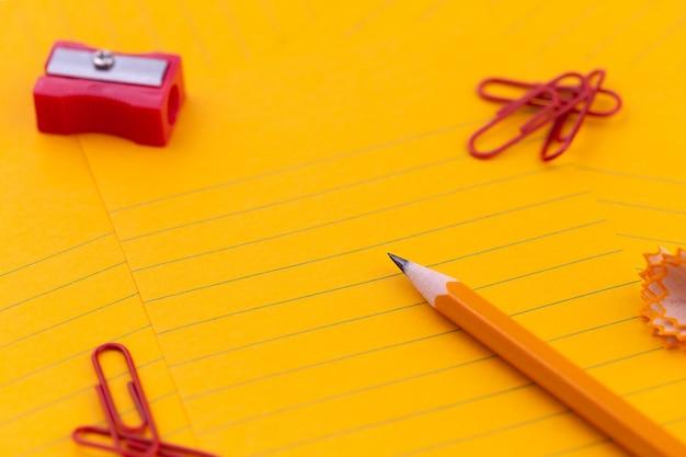 Feuilles de papier orange, crayon, papeterie et un espace vide pour votre texte.