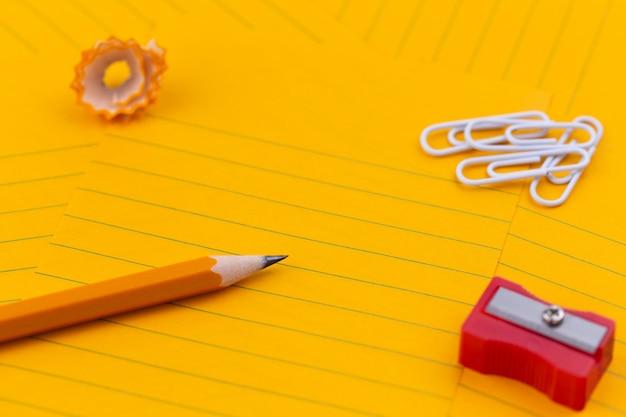 Feuilles de papier orange, crayon, papeterie et espace vide