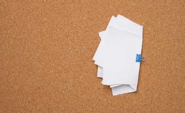 Feuilles de papier vierges blanches reliées avec un clip sur fond marron
