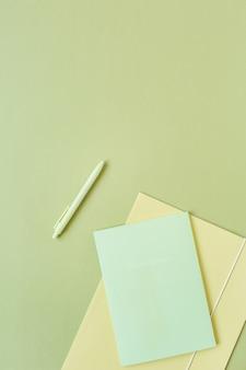 Feuilles de papier vierges, dossier et stylo sur surface verte