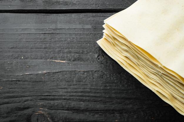 Feuilles de pâtes lasagnes non cuites séchées, ensemble sur table en bois noir