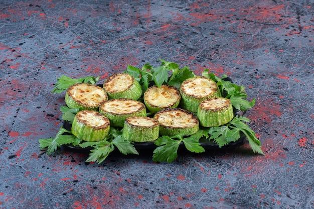 Feuilles de persil ornant un plateau de courgettes frites sur table noire.