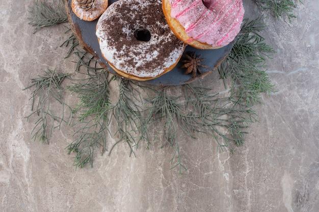 Feuilles de pin sous une planche avec des beignets sur marbre.