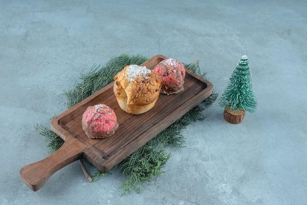 Feuilles de pin sous un plateau en bois avec de petits gâteaux à côté d'une figurine d'arbre sur une surface en marbre