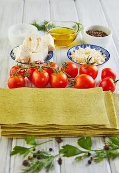 Feuilles pour la cuisson de lasagnes aux épinards, empilées dans une pile et ingrédients tomates cerises, fromage
