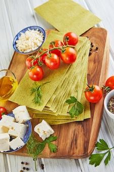 Feuilles pour faire des lasagnes aux épinards et ingrédients: tomates cerises, fromage, beurre, poivrons et herbes.