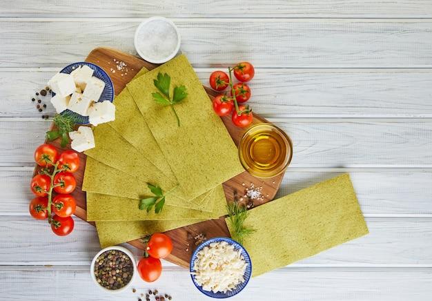 Feuilles pour faire des lasagnes aux épinards et ingrédients tomates cerises, fromage, beurre