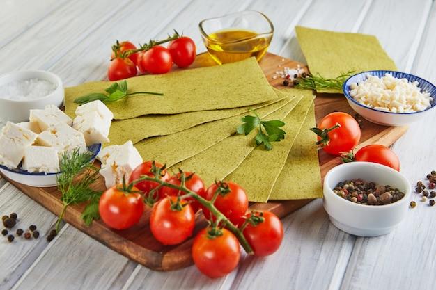 Feuilles pour faire des lasagnes aux épinards et ingrédients tomates cerises, fromage