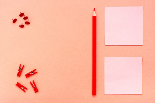 Feuilles pour les notes, les clips et un crayon sur le rouge