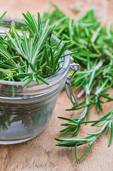 Feuilles de romarin vert fraîchement coupées (rosmarinus officinalis). aspect rustique et en bois. ingrédient de la cuisine méditerranéenne et du remède maison curatif.