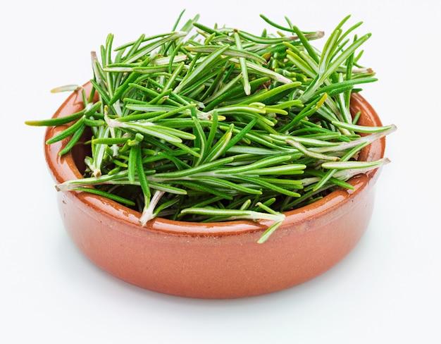 Feuilles de romarin vert fraîchement coupées (rosmarinus officinalis) dans un bol en argile. apparence rustique ingrédient isolé de la cuisine méditerranéenne et du remède maison curatif.