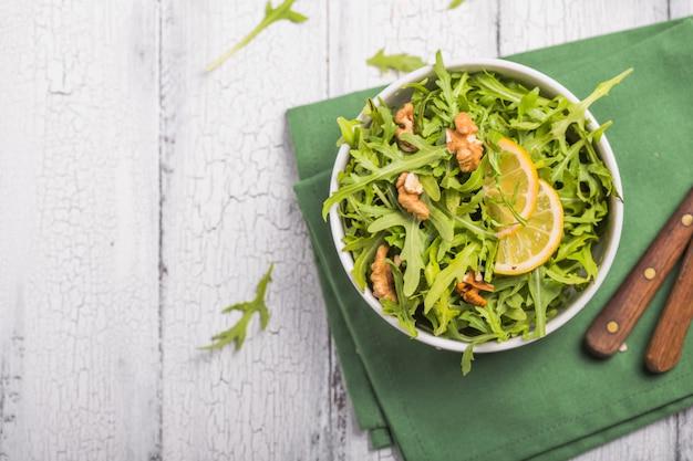 Feuilles de roquette verte fraîche sur bol blanc, salade de roquette sur fond rustique en bois avec place pour le texte. mise au point sélective, alimentation saine, alimentation. concept de nutrition
