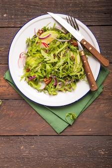 Feuilles de roquette verte fraîche sur bol blanc, salade de roquette à la pomme, radis, noix de pécan, oignon sur fond rustique en bois avec place pour le texte. vue de dessus, alimentation saine, alimentation. concept de nutrition