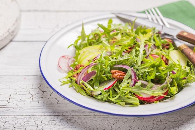 Feuilles de roquette verte fraîche sur bol blanc, salade de roquette à la pomme, radis, noix de pécan, oignon sur fond rustique en bois