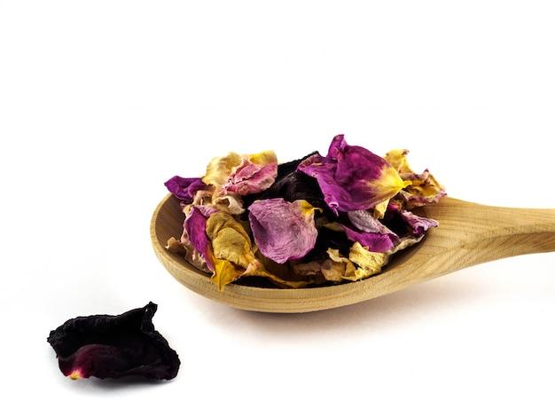 Les feuilles de rose séchées se trouvent dans une cuillère en bois sur un fond blanc