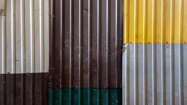 Feuilles rouillées de tôle ondulée de différentes couleurs. fond de texture de clôture ondulée brune, grise, jaune, verte. tôle galvanisée colorée. image de fond de tôles ondulées.