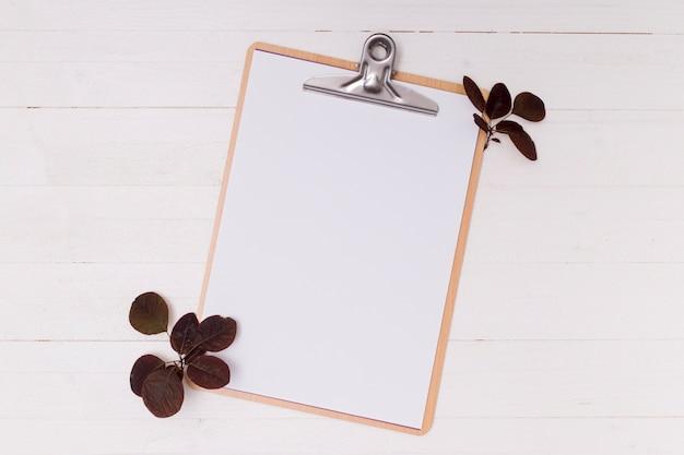 Feuilles séchées avec le presse-papier maquette blanc