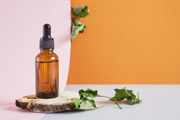 Feuilles sèches et compte-gouttes de bouteille en verre brun sur un podium en dalle de bois sur fond rose, soins de la peau du corps et du visage, sérum ou huile cosmétique dans une bouteille avec une pipette