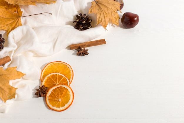 Feuilles sèches, épices, foulard et oranges sur la table. ambiance d'automne, fond, lumière du matin.