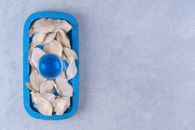 Feuilles sèches et smoothie bleu sur une plaque en bois sur une table en marbre.