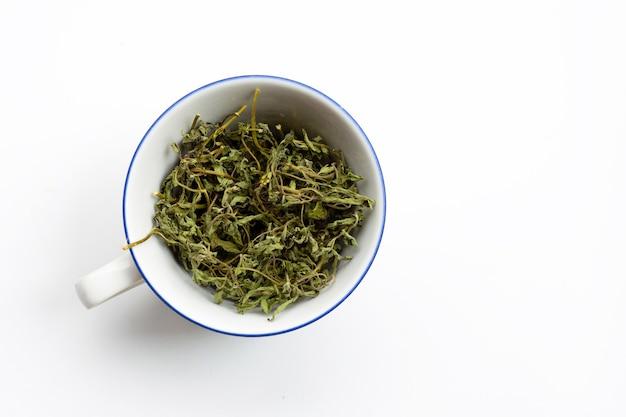Feuilles de stevia sèches dans une tasse blanche sur une surface blanche