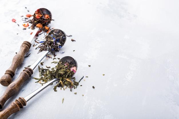 Feuilles de thé assorties, noir, vert, rooibos et fraise dans une cuillère doseuse