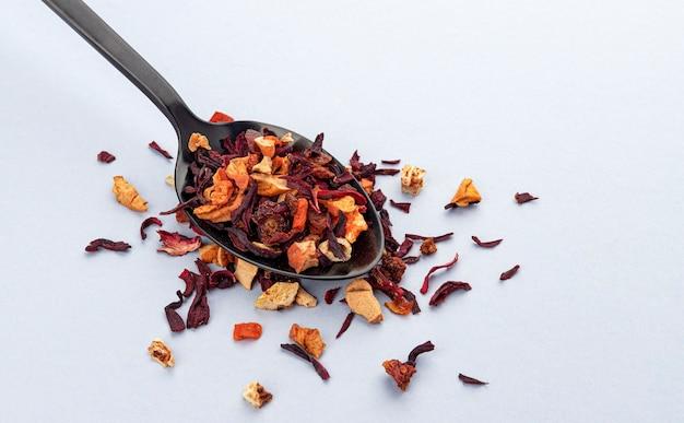 Feuilles de thé aux fruits en cuillère sur fond blanc, thé sec avec des morceaux de fruits et de baies