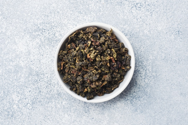 Feuilles de thé à brasser dans un bol sur un fond gris.