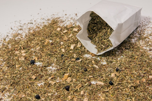 Feuilles de thé sur fond blanc. paquets blancs au thé. paquets blancs avec du thé sur fond blanc. thé aux tranches de fruits et pétales de couleurs