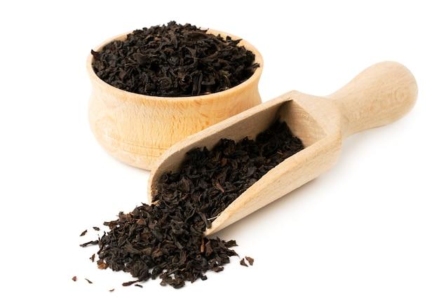 Feuilles de thé noir dans une assiette en bois et cuillère sur blanc, isolé.