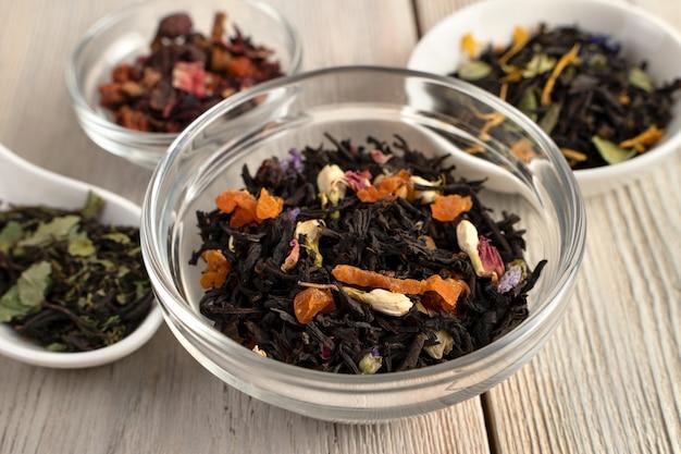 Feuilles de thé noir avec des morceaux de fruits secs et de fleurs