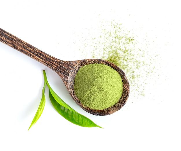 Feuilles de thé et poudre de thé vert matcha en cuillère de bois isolé