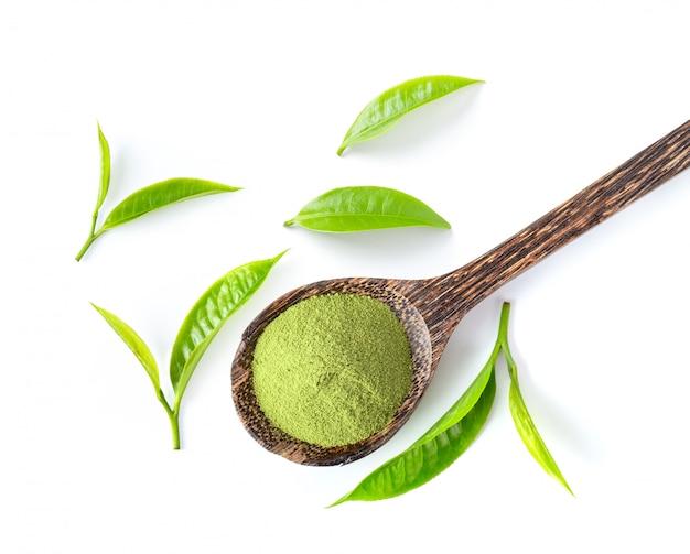 Feuilles de thé et poudre de thé vert matcha dans une cuillère en bois sur un mur blanc.