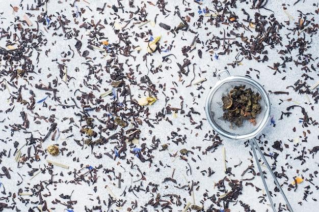 Feuilles de thé pour le brassage dans une passoire sur fond gris. espace de copie.