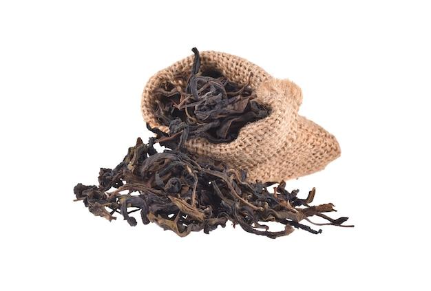 Feuilles de thé sec de sac de jute isolé sur fond blanc.