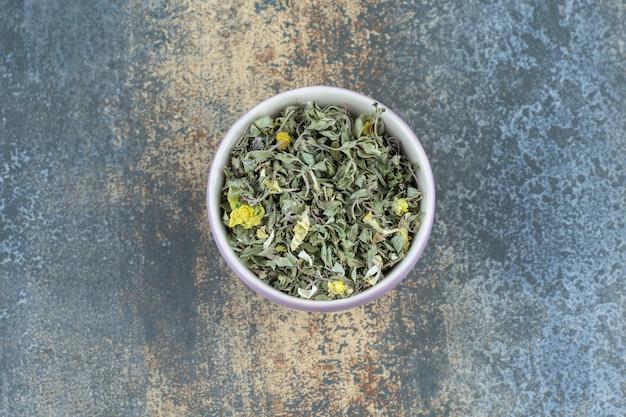 Feuilles de thé séchées biologiques dans un bol blanc.