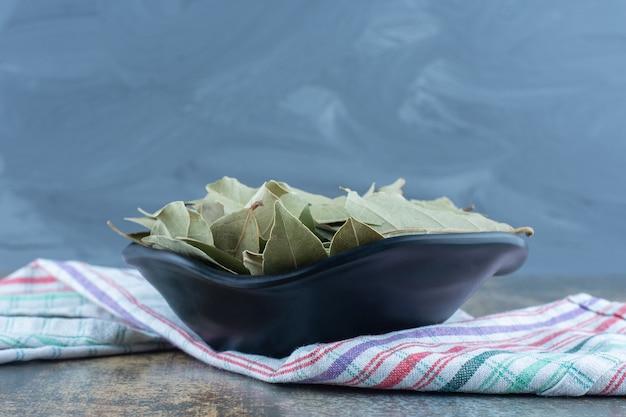 Feuilles de thé séchées dans un bol noir.