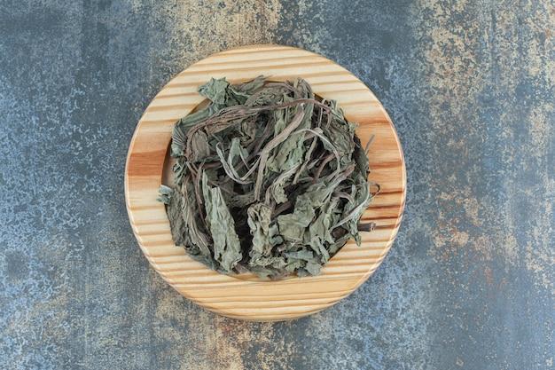 Feuilles de thé séchées sur plaque de bois.
