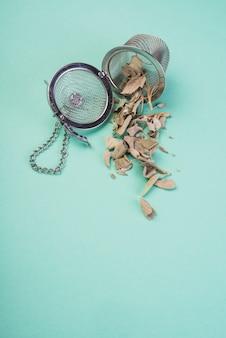 Feuilles de thé séchées en vrac sur des passoires à thé sur fond coloré