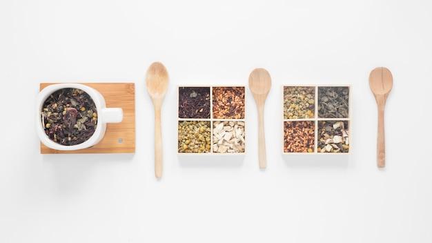 Feuilles de thé sèches; herbes et cuillère en bois disposées dans une rangée sur fond blanc