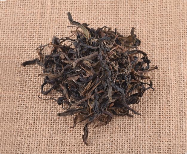 Feuilles de thé sèches isolées sur fond de toile de jute.