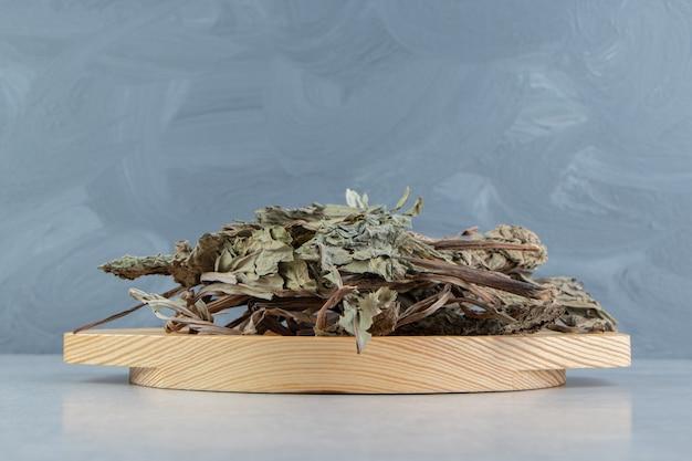 Feuilles de thé sèches sur plaque de bois.