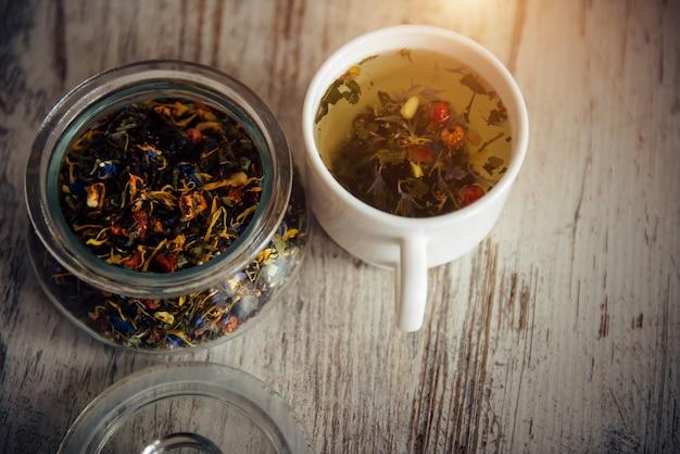 Feuilles de thé et thé sur fond de bois vintage, vue de dessus, gros plan. lumière du matin. tisane combinée avec des baies dans un bol en verre. concept de soins de santé, boissons naturelles, spa, produits biologiques.